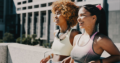 Buy stock photo Cropped shot of two attractive young girlfriends taking a break from working out in the city during the day