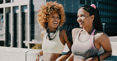 Buy stock photo Cropped shot of two attractive young girlfriends having a chat while working out together in the city