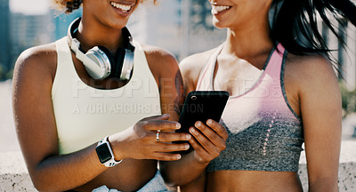 Buy stock photo Cropped shot of two unrecognizable sportswomen using a smartphone together outdoors in the city