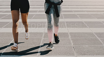 Buy stock photo Cropped shot of two unrecognizable sportswomen jogging together outdoors in the city