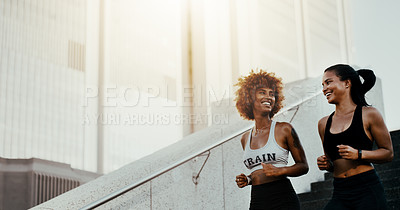 Buy stock photo Cropped shot of two attractive young sportswomen jogging together outdoors in the city