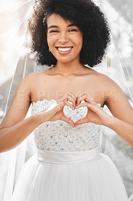 Buy stock photo Portrait of a happy and beautiful young bride making a heart shape with her hands outdoors on her wedding day