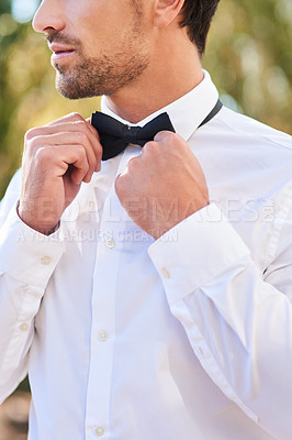 Buy stock photo Cropped shot of an unrecognizable young bridegroom putting on a bowtie while standing outdoors on his wedding day