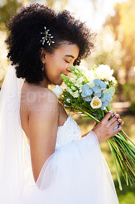Buy stock photo Shot of a happy and beautiful young bride smelling her bouquet of flowers outdoors on her wedding day