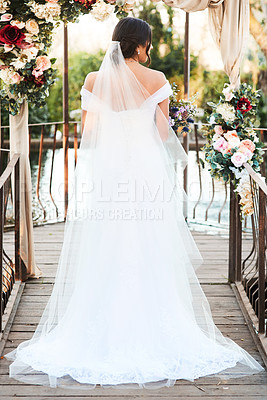 Buy stock photo Rearview shot a beautiful young bride standing outdoors on her wedding day