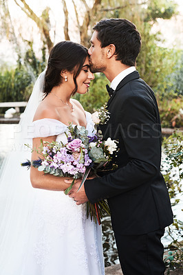Buy stock photo Shot of a happy newlywed young couple posing together outdoors on their wedding day