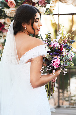 Buy stock photo Shot of a happy and beautiful young bride holding her bouquet of flowers while posing outdoors on her wedding day