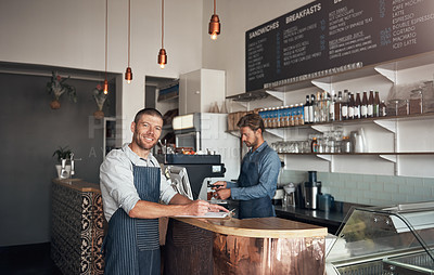 Buy stock photo Portrait of a mature man writing on a clipboard while working in a cafe with his colleague in the background