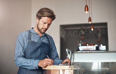 Buy stock photo Shot of a young man writing on a clipboard while working in a cafe