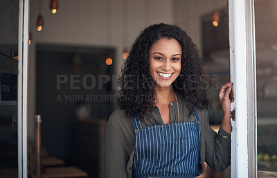 Buy stock photo Portrait of a young woman standing at the doorway of her cafe