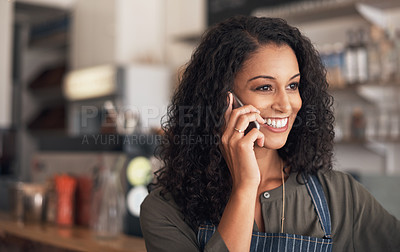 Buy stock photo Shot of a young woman talking on a cellphone while working in a cafe