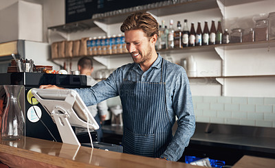 Buy stock photo Shot of a young waiter working on a till in a cafe