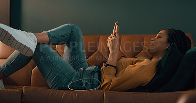 Buy stock photo Shot of an attractive young woman using her cellphone while relaxing on a sofa at home