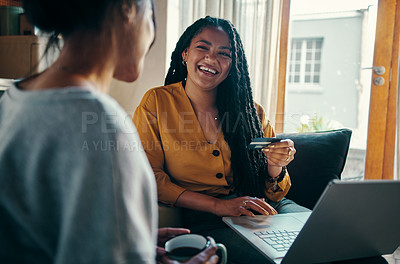Buy stock photo Shot of two attractive young women using a credit card and laptop to shop online together while relaxing at home