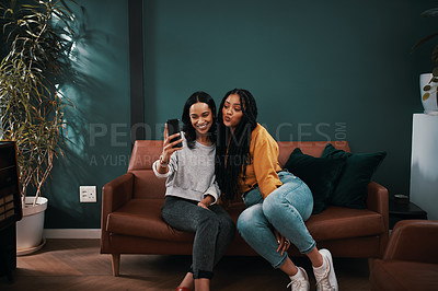 Buy stock photo Full length shot of two attractive young women taking selfies with a cellphone while relaxing together at home