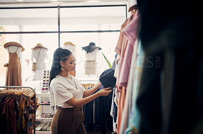 Buy stock photo Cropped shot of a woman looking at a hat in a clothing store
