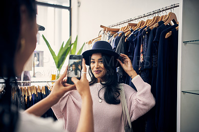 Buy stock photo Cropped shot of a young woman taking a picture of her friend trying on a hat