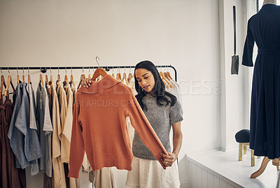 Buy stock photo Cropped shot of a beautiful young woman holding up a garment in a clothing store