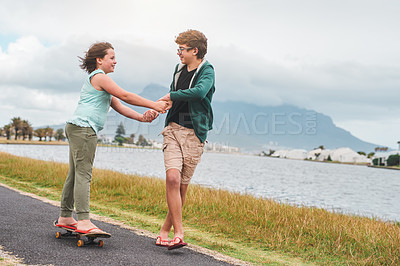 Buy stock photo Full length shot of a happy young girl skateboarding outdoors while holding her brother's hands