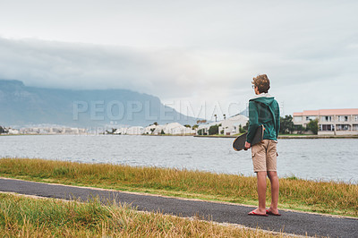 Buy stock photo Full length shot of an unrecognizable boy standing outside alone and holding his skateboard while looking out at the lake