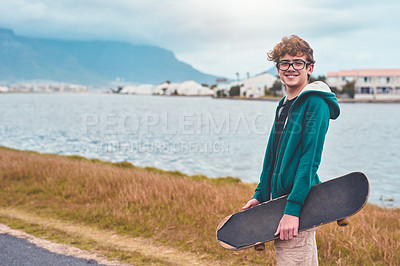 Buy stock photo Cropped portrait of an unrecognizable boy standing outside alone and holding his skateboard while looking out at the lake