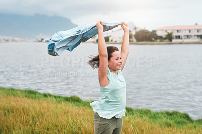 Buy stock photo Cropped shot of a happy young girl standing outside alone and holding her shirt above her head in the wind