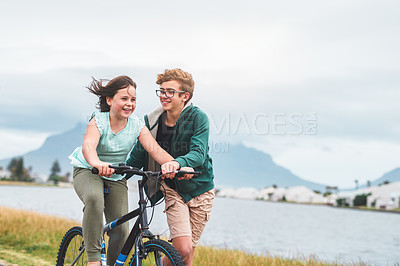 Buy stock photo Cropped shot of a happy young boy helping his little sister ride a bicycle during a day out