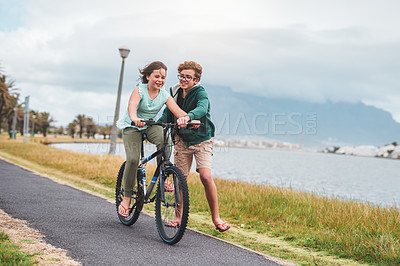 Buy stock photo Full length shot of a happy young boy helping his little sister ride a bicycle during a day out