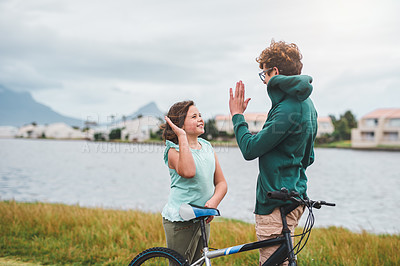 Buy stock photo Cropped shot of two young siblings standing together and giving each other a high five after riding a bicycle