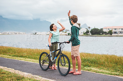 Buy stock photo Full length shot of two young siblings standing together and giving each other a high five after riding a bicycle