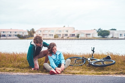 Buy stock photo Full length shot of a young boy kneeling next to his injured sister and comforting her during a day out