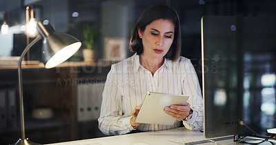 Buy stock photo Cropped shot of an attractive young businesswoman using a digital tablet while working late in a modern office