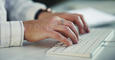 Buy stock photo Cropped shot of an unrecognizable businesswoman typing on a computer while working late in a modern office