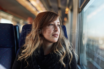 Buy stock photo Cropped shot of an attractive young woman sitting alone on a train and looking contemplative during her commute