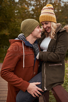 Buy stock photo Cropped shot of an affectionate young couple spending time together at a park in late autumn