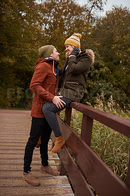 Buy stock photo Full length shot of an affectionate young couple smiling at each other while spending time together in a park in late autumn