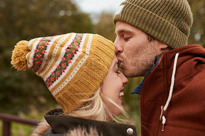 Buy stock photo Cropped shot of an affectionate young man kissing his girlfriend on the forehead while standing in a park in late autumn