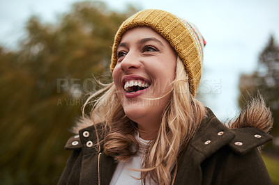 Buy stock photo Cropped shot of an attractive young woman smiling while standing in a park in late autumn
