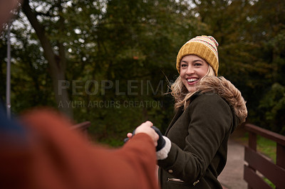 Buy stock photo Cropped shot of an affectionate young woman pulling her boyfriend's hand in a park in late autumn