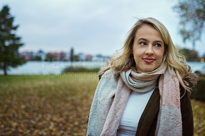 Buy stock photo Cropped shot of an attractive young woman standing in a park in late autumn
