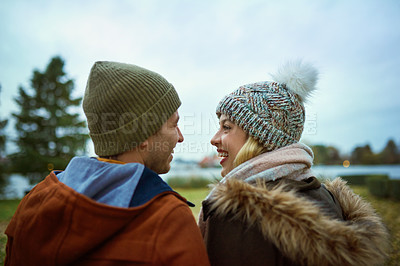 Buy stock photo Rearview shot of an affectionate young couple smiling at each other while standing in a park in late autumn