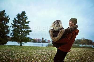 Buy stock photo Cropped shot of an affectionate young man lifting his girlfriend in a park in late autumn