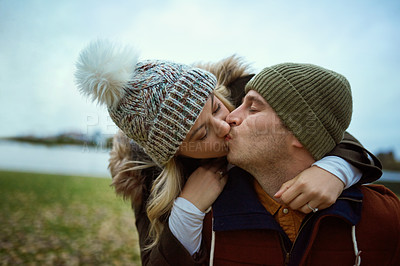 Buy stock photo Cropped shot of an affectionate young man kissing his girlfriend while piggybacking her in a park in late autumn