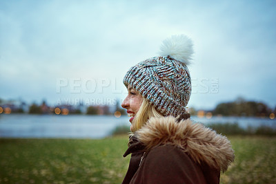 Buy stock photo Cropped shot of an attractive young woman smiling while standing in park in late autumn