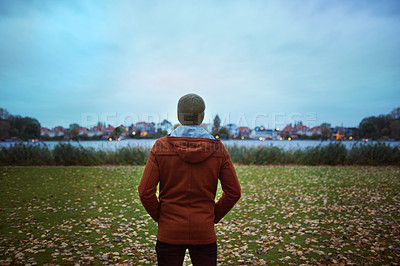 Buy stock photo Rearview shot of an unrecognizable man looking at the view while standing in a park in late autumn