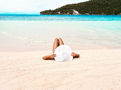 Buy stock photo Rearview shot of a beautiful young woman relaxing on the beach