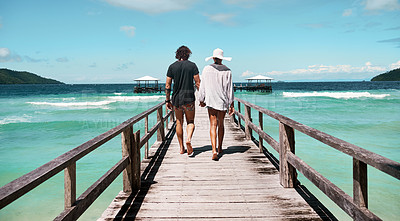 Buy stock photo Rearview shot of a carefree young couple walking on a jetty together next to the ocean during the day