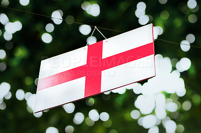Buy stock photo Shot of the flag of England hanging outside under a tree