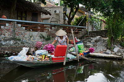 Buy stock photo Shot of a woman selling various goods from a boat on a river in Vietnam