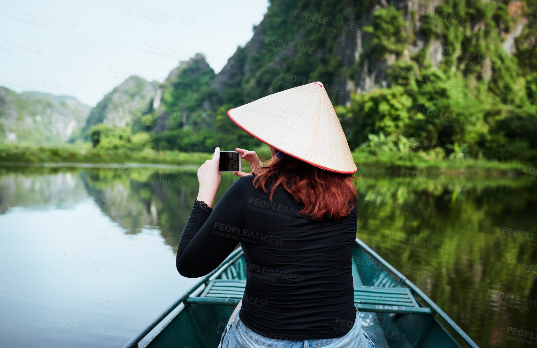 Buy stock photo Rearview shot of a young woman taking pictures on her smartphone while riding a boat down a river in Vietnam